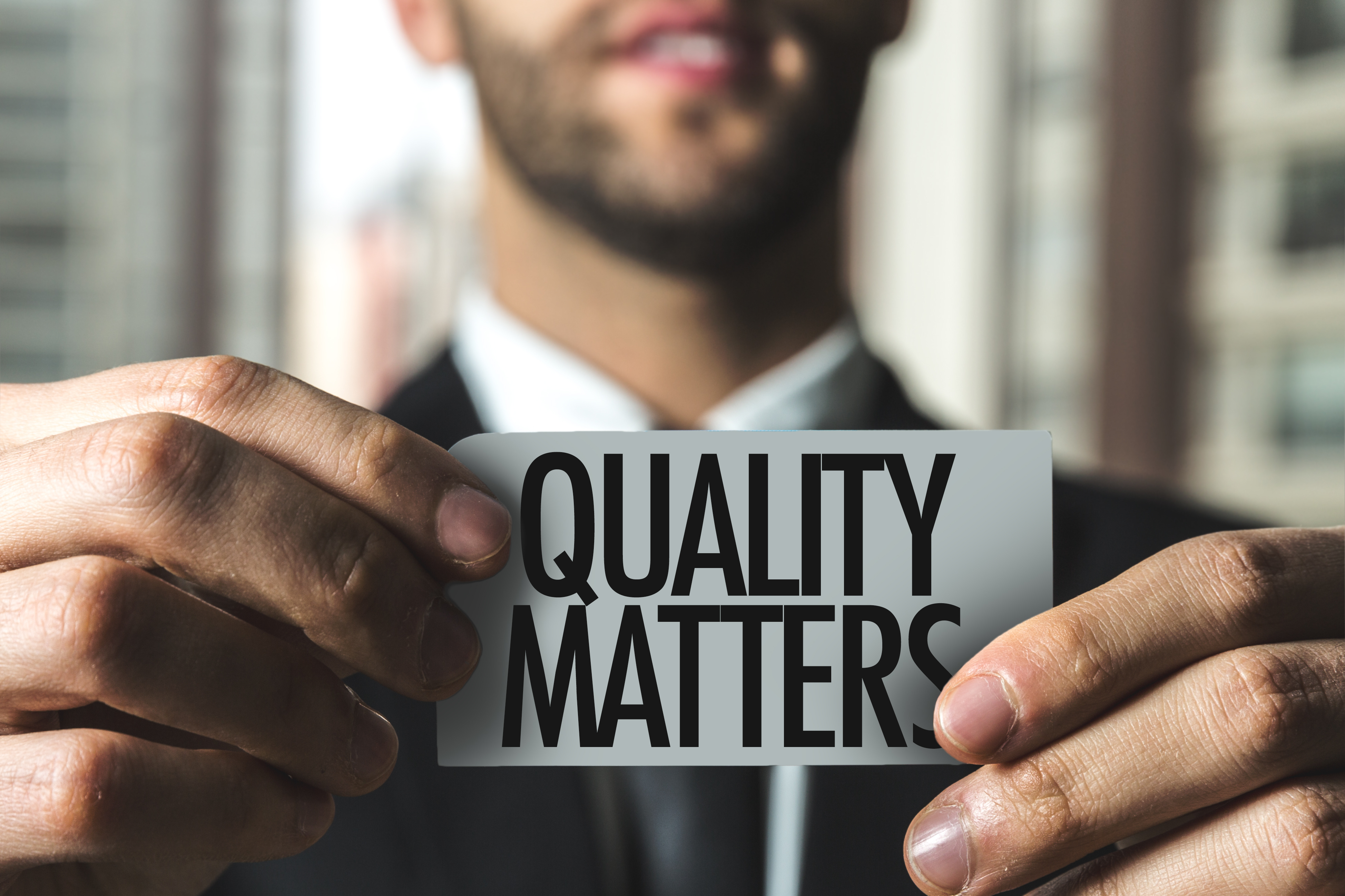 Businessmen holding Quality Matters Tag